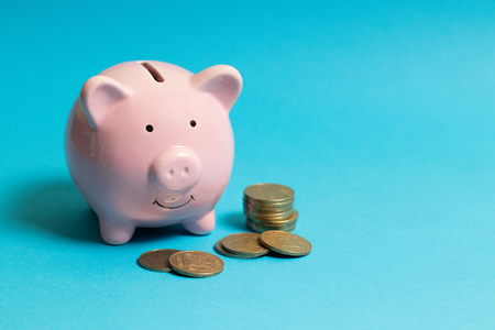 Piggy bank with gold coins on blue background. Commercial concept. Foto de archivo