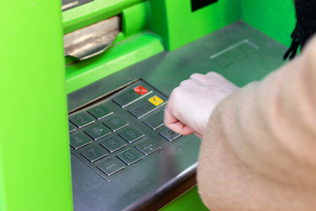 Close Up of woman entering her pin code on keyboard of ATM