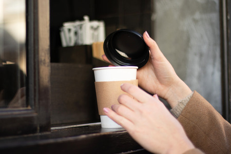 Buying coffee in an outdoor cafe. The hand of the girl takes a paper cup with a drink tea, coffee, cocoa . Stock Photo