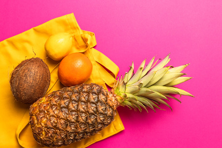 Composition of various fresh exotic fruits with a yellow cotton bag on a yellow background. Flat lay. Food concept.