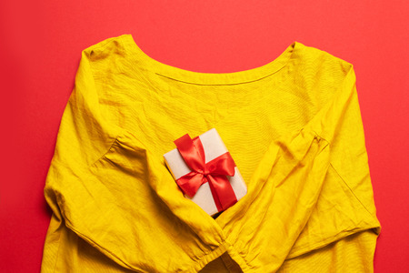Women's yellow cotton blouse and and gift box on red background. Flat lay, top view, copy space