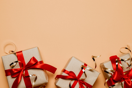 Top view of presents boxes with red bows and confetti on pastel table with copy space for text. Top view, flat lay. Stockfoto