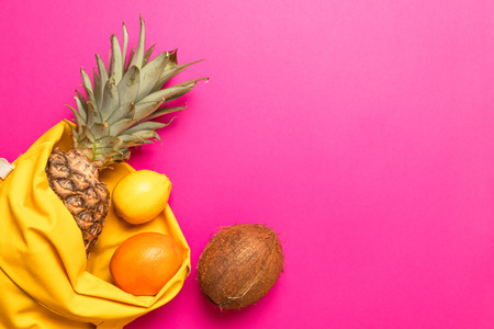 Summer, holiday concept. Tropical fruits with a yellow cotton bag on a pink background