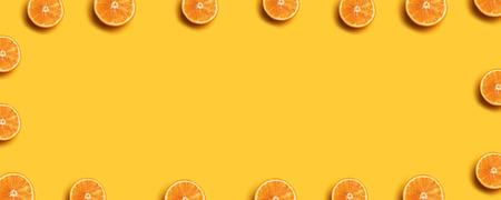 Creative summer pattern made of fresh orange slices on yellow background. 版權商用圖片
