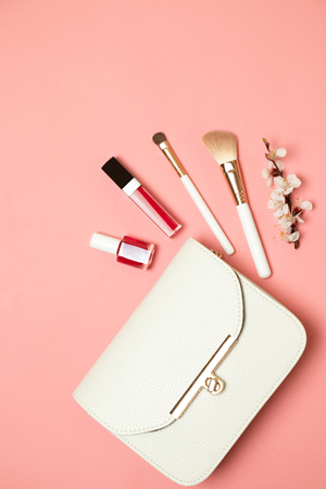 Cosmetic bag with beauty accessory and makeup product. Flat lay