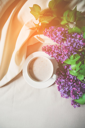 Morning romantic composition cup of coffee with a book and a bouquet of lilacs on the bed 写真素材