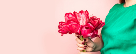 Woman hand with manicure holding tulips flowers on pink background. Greeting card for International Womans Day, Mothers Day, mockup, copy space