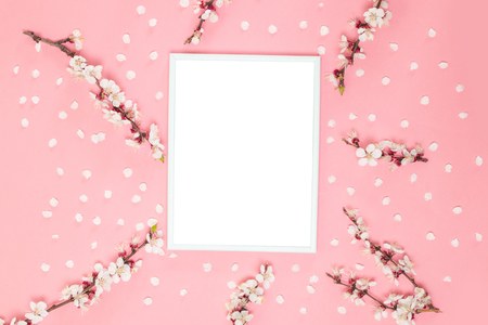 Spring composition. Photo frame with twigs of flowers on a pink background. Top view, flat lay. Layout for a party or birthday invitation.