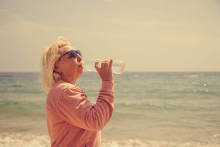 Adult blonde woman drinks water from a bottle on the sea coast