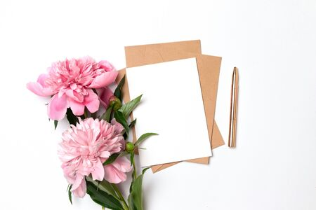Creative mockup of craft envelope with a sheet of paper with a bouquet of pink peonies on a gray background