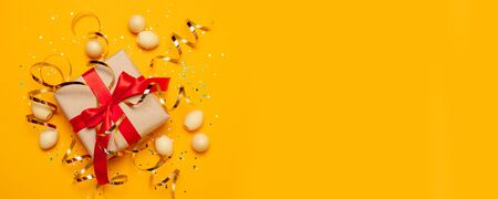 Holiday composition of surprise box with red bow ribbon, candy eggs, confetti and golden ribbon decor on bright yellow background.