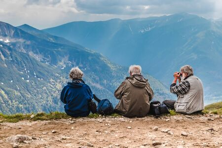 Polish Tatras, Poland June 3 2019: Three elderly people with backpacks are sitting on in the mountains. Old man looks through binoculars. The couple enjoys beautiful views of hilly mountains.