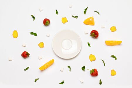 Flat lay concept empty white plate, sugar cubes, strawberries, ginger slices, orange and mint leaves. Objects are arranged in the form of a circle. Banque d'images