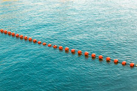 Orange buoys in the sea. Separation buoys in the river for safe swimming on the beach.