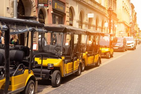 Stockholm, Sweden June 7 2019: Urban tourism. Yellow small outdoor sightseeing cars along the street on a sunny day