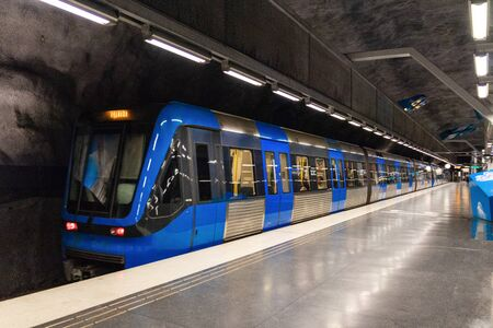Stockholm, Sweden June 7 2019: Modern illuminated Solna Strand Underground Subway Station in gray colors with blue moving train. 新聞圖片
