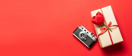 Old retro vintage camera, gift box with red ribbon on red background, top view flat lay with copy space.