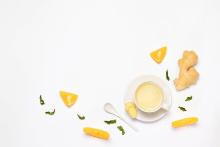 Creative layout of a cup of hot tea with ginger and slices of oranges on a white background. View from above
