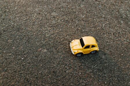 Odessa, Ukraine April 7 2019: Yellow toy car on the beach in the sunlight in summer. Vacation and travel concept. Sunrise on tropical island beach and car miniature