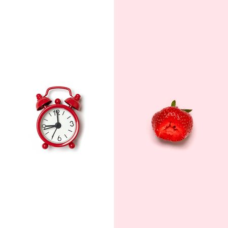 Creative picture of a red alarm clock and a red strawberry on a white background. Top view, flat lay, copy space. Concept of diet and detox time or summer time menu. Banco de Imagens