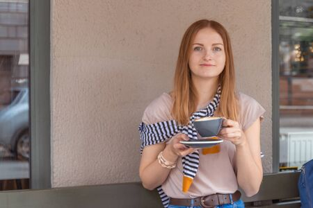Woman drinks coffee at the table of cafe in summer day outdoor.