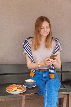 Caucasian female watching her photos on cell telephone while relaxing in cafe during free time Stok Fotoğraf