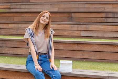 Smiling blonde student girl in t-shirt and blue jeans is sitting on a wooden bench and a paper bag on a sunny day in the park. Lunch break. Empty space for design Stok Fotoğraf