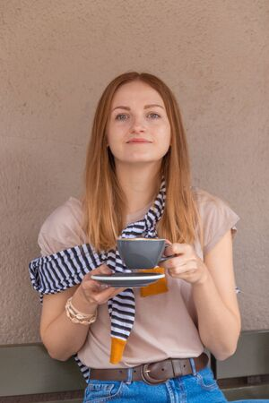 Young charming woman sitting alone in a cafe in her free time, attractive woman with a sweet smile with a cup of coffee while relaxing in a cafe 版權商用圖片
