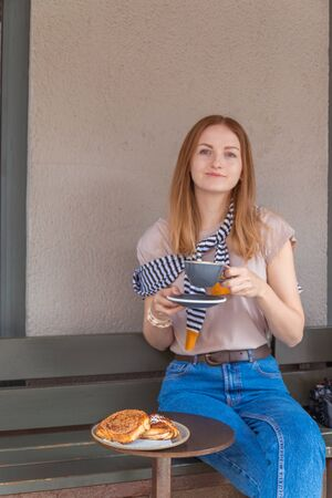 Pleasant time and relaxation. Girl relax cafe with coffee and dessert. Young woman having a breakfast with coffee and cake sitting outdoors in a cafe