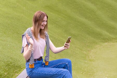 Portrait of a beautiful young blonde standing by a mobile phone against a park on a sunny day Stok Fotoğraf