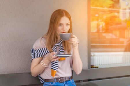 Cute girl holding a cup of coffee with a saucer sitting in a cozy cafe on the street on a sunny summer day Stok Fotoğraf