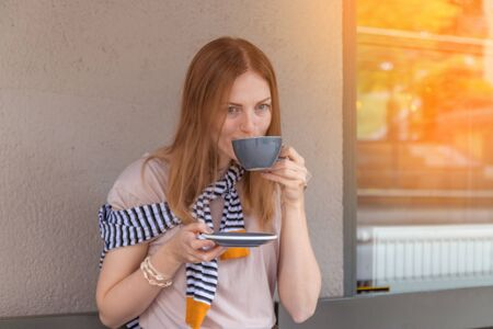Young charming woman sitting alone in a cafe in her free time, attractive woman with a sweet smile with a cup of coffee while relaxing in a cafe Stock Photo
