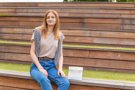 Smiling blonde student girl in t-shirt and blue jeans is sitting on a wooden bench holding a doggy bag on a sunny day in the park. Lunch break. Empty space for design