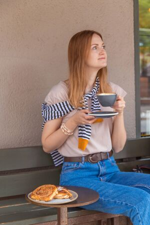 Details of the accessories of a pretty woman in stylish clothes, holding a cup of coffee with a bun with sugar on a metal table sitting in a street cafe