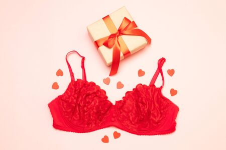 Flat lay of red Christmas underwear with gifts and accessories on a pink background. Imagens