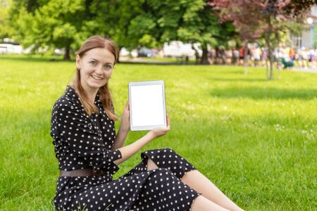 Happy young blonde haired girl in a pea dress texture lying on the grass and using a tablet, watching an educational video in a park outdoors.