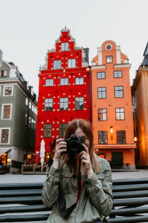 Hipster hiker tourist taking photo on camera on background of atmospheric city with beautiful colorful houses of Stockholm, photographer woman enjoying light of holiday