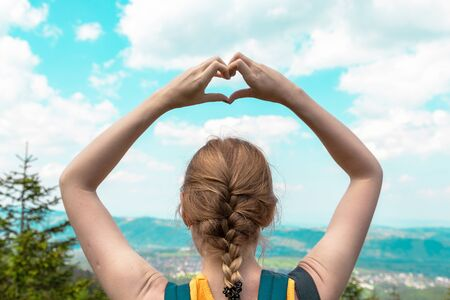 Hands heart love symbol shaped women traveling lifestyle charity help concept vacations in mountains landscape