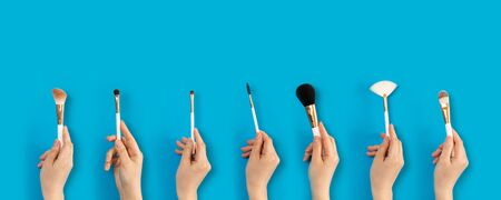 Female hand holds natural bristles of makeup brushes with a plastic handle on a blue background. Banco de Imagens