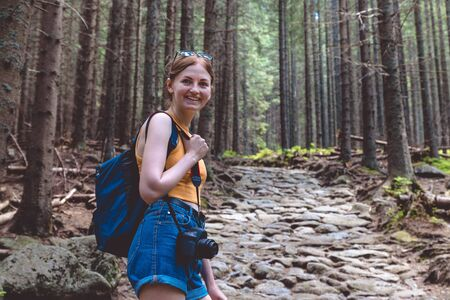 Blonde woman tourist with a backpack and in shorts travels through the forest