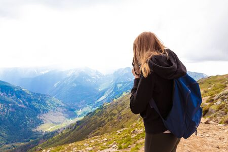 Travel and blogging concept. Young girl in a black sweater and leggings stands in the mountains and photographs the nature of beauty.
