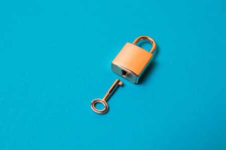 Flat lay protection concept. Locked padlock and key on the blue background.