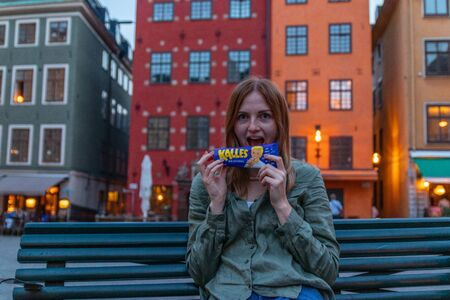 Stockholm, Sweden June 7 2019: Woman hand holding tube with Kalles origianl caviar sitting on a bench in the evening on the streets