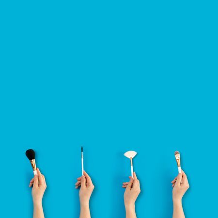 Set of different make-up brushes with hand, isolated on blue background. Woman using make-up brush Stok Fotoğraf