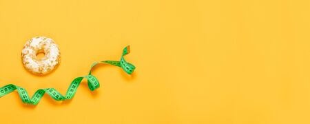 Sweet gingerbread and ribbon on orange background. Healthy lifestyle and diet concept.