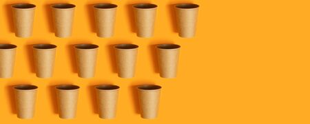 Paper cups on orange background with copy space. Minimal flat lay