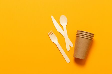 Disposable paper cups and wooden cutlery on table. Minimal flat lay