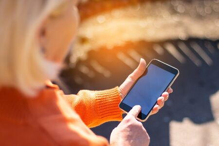 Blonde woman using social networks, watches video on phone on sunny day