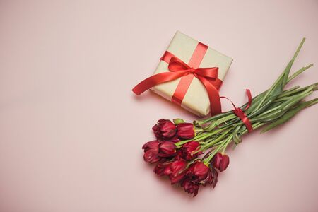 Flat lay composition bouquet of red tulips with gift boxes satin ribbon on pink background with empty space in center, top view