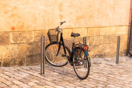 Black bike parked against yellow wall in the street of Stockholm. Old city summertime
